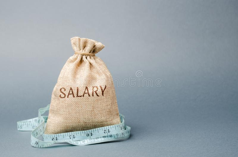 Money bag with the word Salary and tape measure. Wage cuts. The concept of limited profit. Lack of money and poverty. Small income stock images