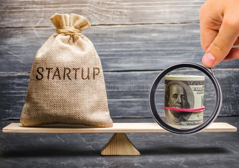 Money bag with the word Startup and dollars on the scales. Analysis of funds raised and verification of the goals of a startup. stock photography