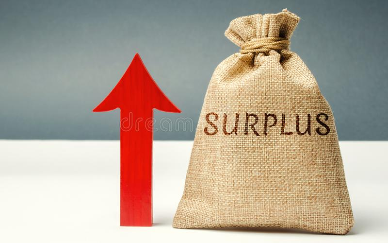 Money bag with the word Surplus and up arrow. The concept of increasing budget surplus. Economic prosperity. Cash receipts are stock image