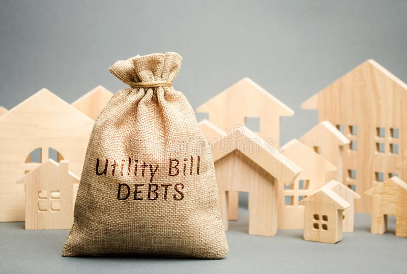 Money bag with the words Utility bill debts and wooden houses. Fines and penalties for failure to pay the debt for electricity and. Gas. Register of debtors royalty free stock photo