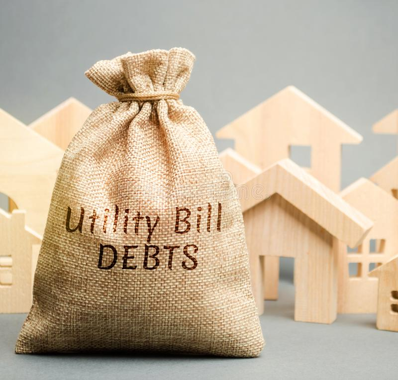 Money bag with the words Utility bill debts and wooden houses. Fines and penalties for failure to pay the debt for electricity and. Gas. Register of debtors royalty free stock images
