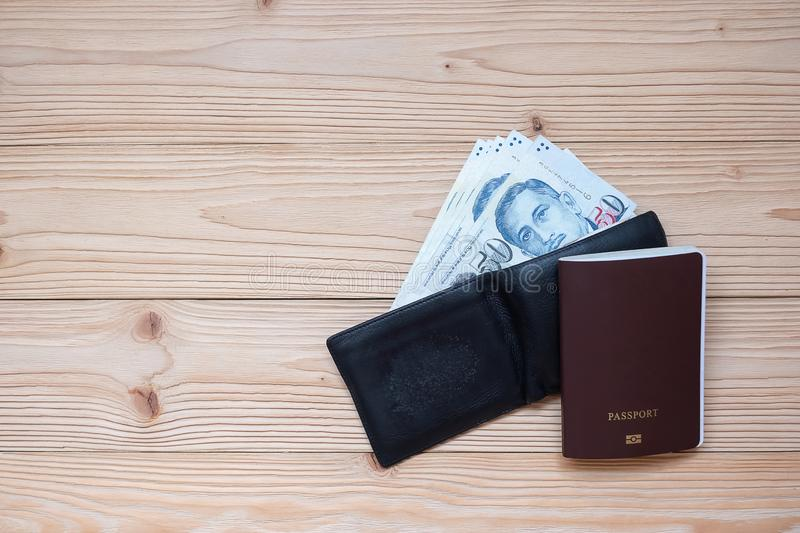 Money banknote in black wallet with Passport on wooden table, Top view and copy space. Time to Travel in Singapore concept royalty free stock photography