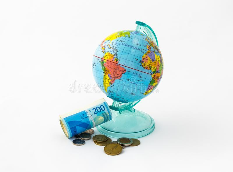 A money box made in the form of a globe, the planet Earth with a money slot at the top stands near a rolled up and held together s royalty free stock photography