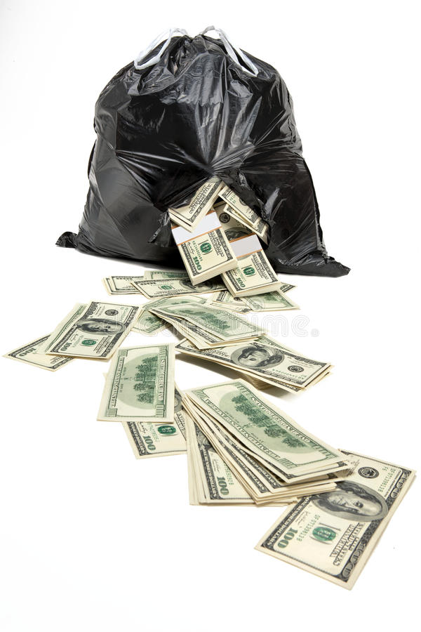 Money in the broken bag. Studio photography of black plastic bag with hundred dollar bills on a white background royalty free stock photography