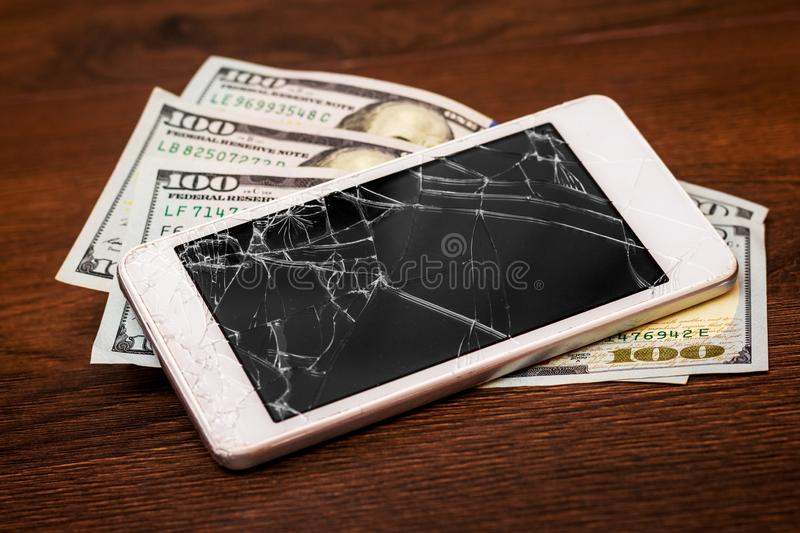 Money and broken cellphone on a wooden table. Payment for phone repair. Smartphone repair costs_ royalty free stock photos