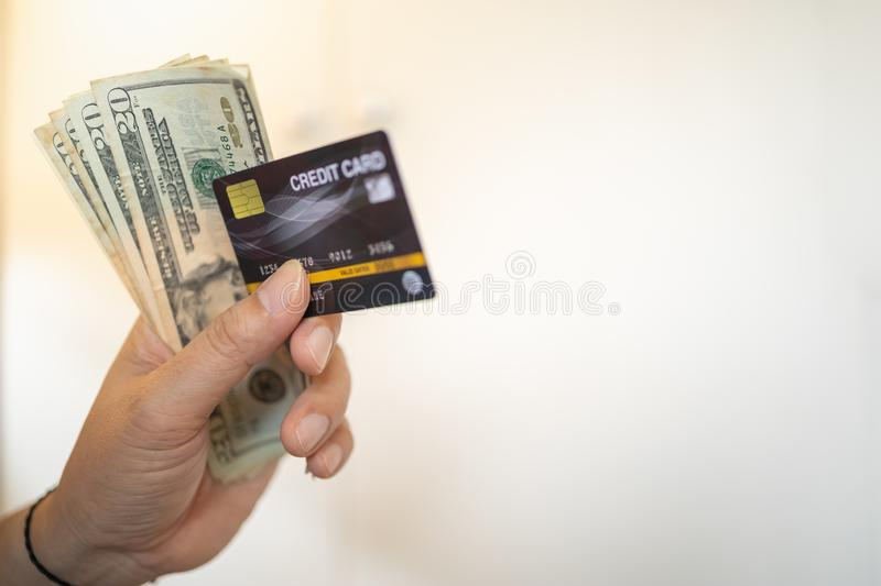 Money and Business concept. Close up of man hand holding credit card and 20 US dollars banknote with copy space royalty free stock photos