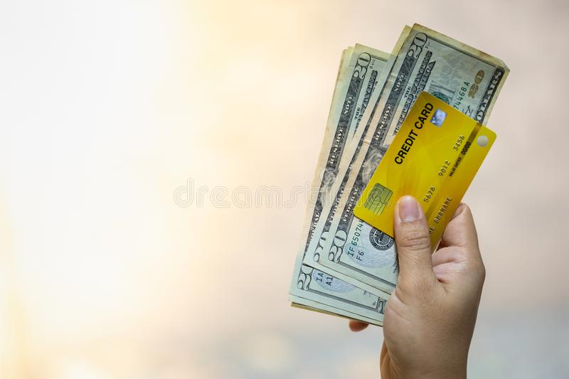 Money and Business concept. Close up of woman hand holding credit card and 20 US dollars banknote with copy space royalty free stock photos