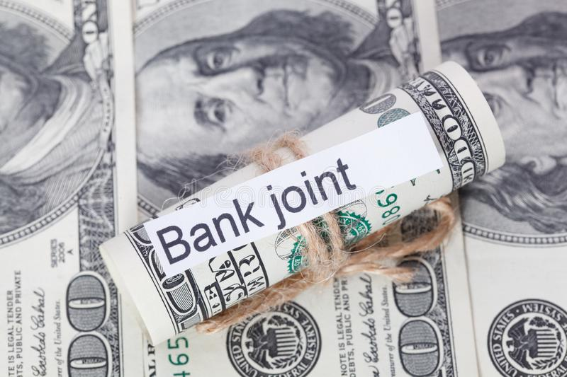 Money and business idea, The dollar bills tied with a rope, with a sign - Bank Joint. Money and business idea, The dollar bills tied with a rope, with a sign royalty free stock image