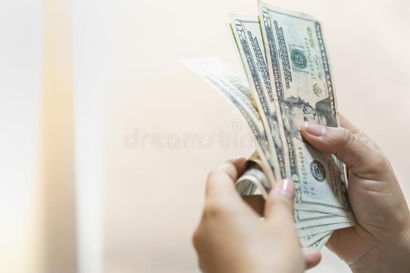 Money Business shopping and saving concept. Close up of woman hand holding and counting US Dollar banknote with copy space royalty free stock photo