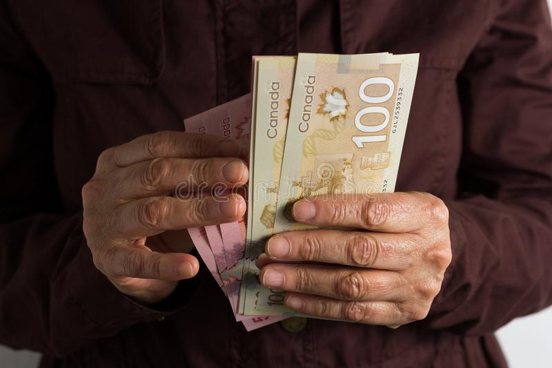 Money from Canada: Canadian Dollars. Front view senior person holding bills stock photo
