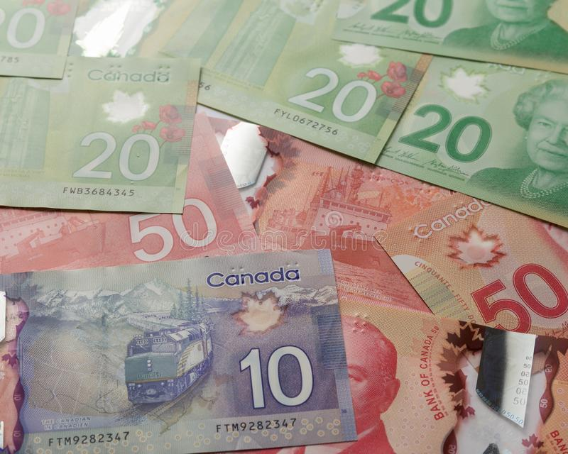 Money from Canada: Canadian Dollars. Full frame of bills spread on table and assorted amounts. Pile of money stock photography