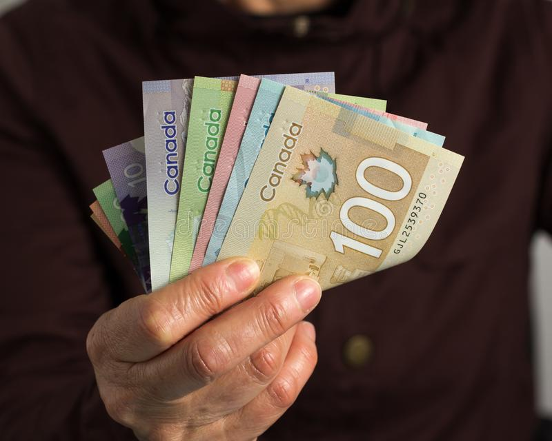 Money from Canada: Canadian Dollars. Old retired person paying in cash stock photos