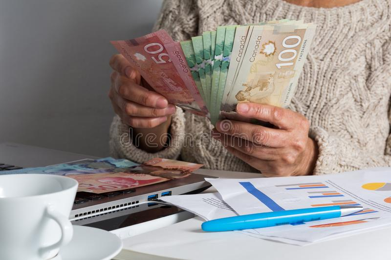 Money from Canada: Canadian Dollars. Senior person handling bill on desk royalty free stock photography