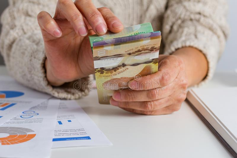 Money from Canada. Dollars. Person handling papernotes on desk stock images