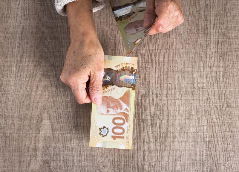 Money from Canada. Dollars. Top view of old woman`s hand handlin stock photos