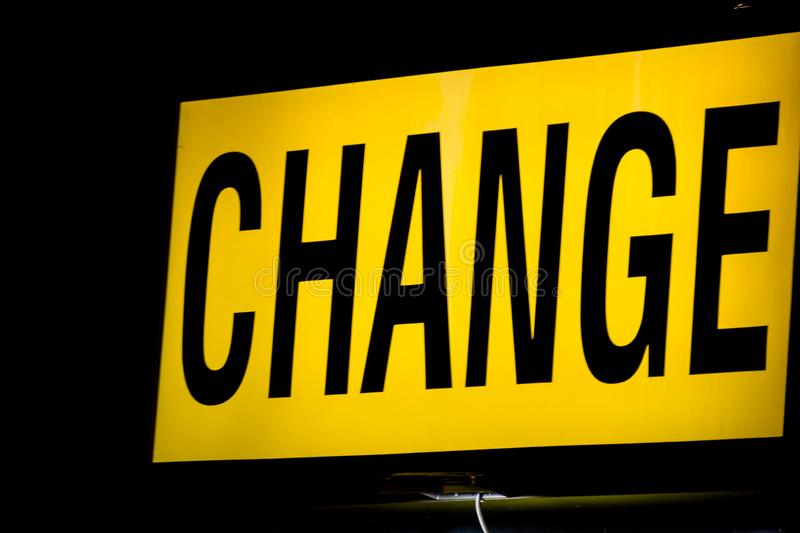 Money change. Glowing Lettering `Change` - the place to exchange money in the streets. Yellow background and black letters stock image