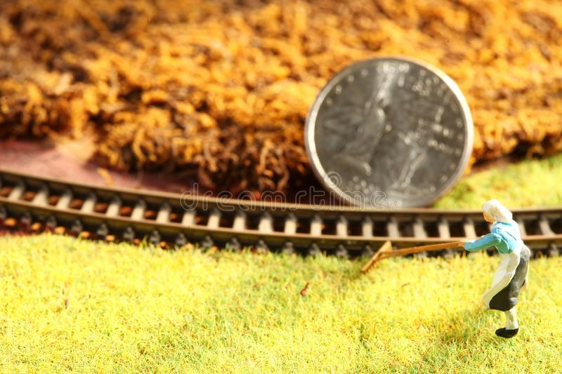 The money coin put on the miniature model railroad scene royalty free stock images