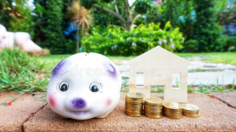 Money. Coins bank resort money wood pig piggy travel tree success payment home house green garden close-up rich business value economy banking cash currency stock photo