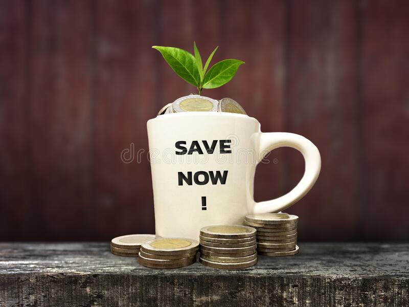 Money coins in a cup on a wood background royalty free stock images
