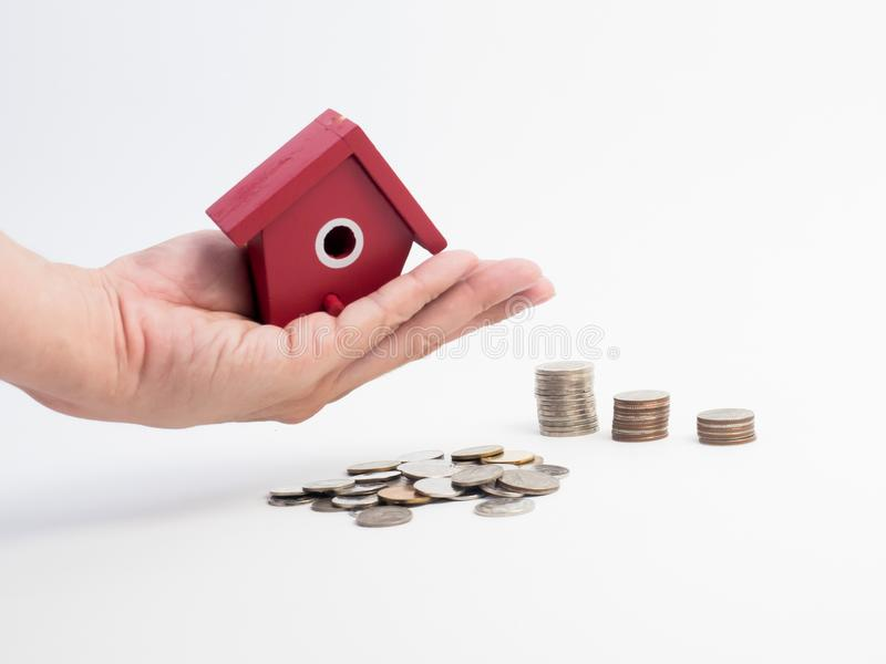 Money coins stack growing with red house on wood background. Business growth investment and financial concept ideas.Real estate in. Vestment. House and coins on stock photo