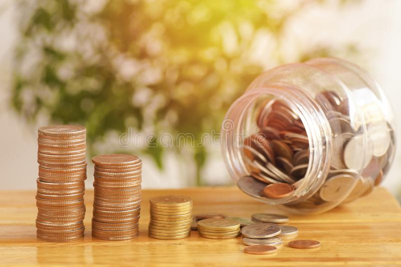 Money coins stacked on wood table with plastic jarsr, concept in save growth up step by step of business, finance, economy and acc. Money coins stacked on wood royalty free stock image