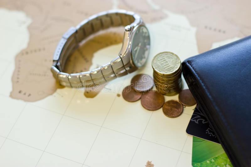 Money concept: сoins, purse, credit cards,wristwatch. Background - map of the world royalty free stock images