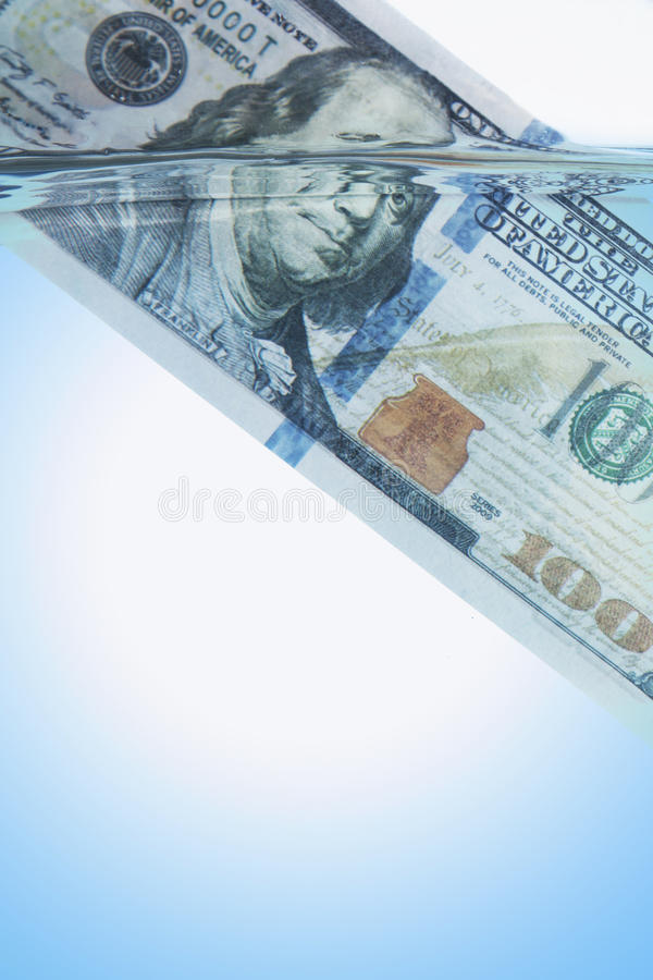Money concept showing US Dollar sinking in шатер as a symbol of global economic crisis stock images
