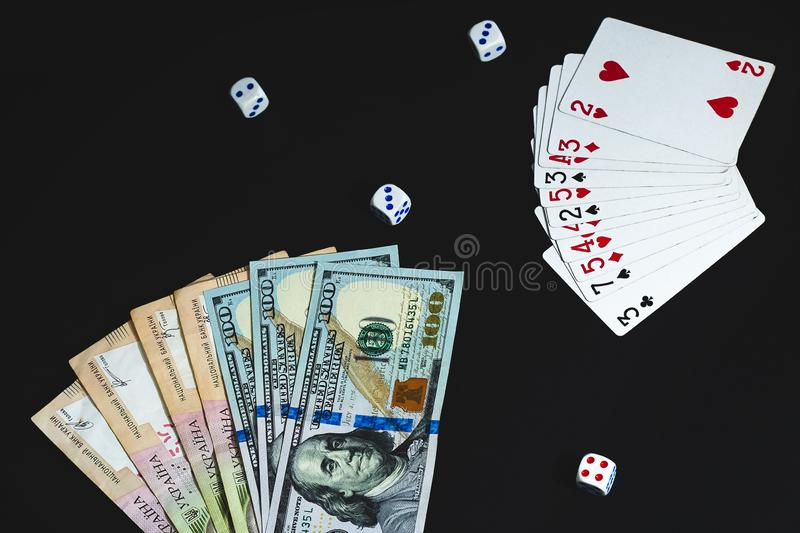 Money, dices and cards on a black background. Close-up stock image