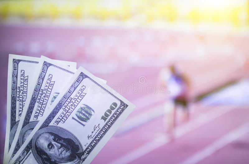Money dollars against the background of the TV, which shows athletics, jogging, sports betting, bookmaker. Dollars royalty free stock images