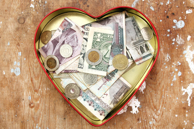 Money donation and saving in heart box. Money donation in heart colorful box on rusted wooden background