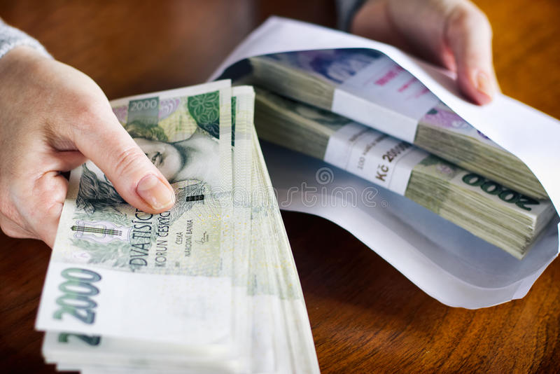 Money in an envelope as a symbol of corruption. Taking bribes, Czech currency in criminal activity. Woman inserts financial bribe in an envelope stock photos