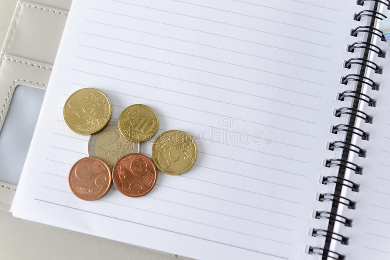 Money euro coins on notebook royalty free stock photography