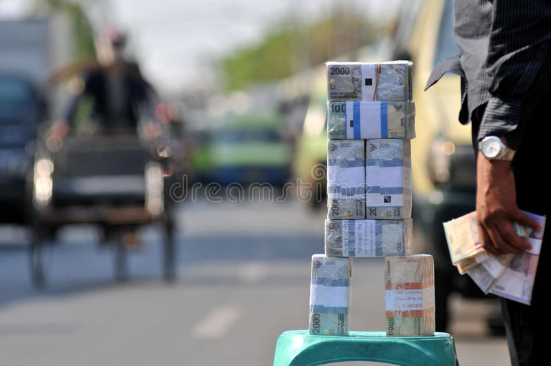 Money Exchange Services. A seller of small denomination currency exchange services new hawking new money with a variety of fractions in Surabaya, East Java royalty free stock images