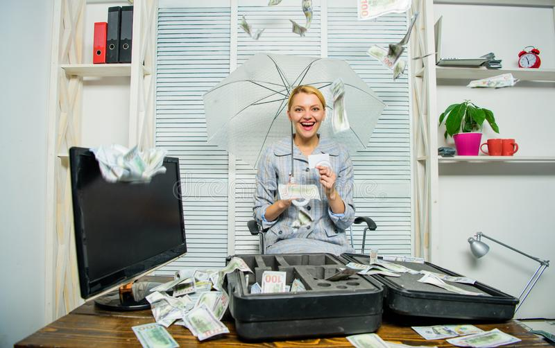 Money falling from ceiling. Woman business lady or accountant under umbrella. Financial success. Accountant with pile stock photo