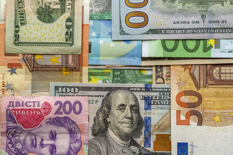 Money and finances concept. One hundred dollar new bill on colorful abstract background of Ukrainian, American and euro national stock photos
