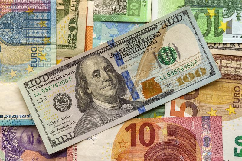 Money and finances concept. One hundred dollar new bill on colorful abstract background of Ukrainian, American and euro national royalty free stock photo