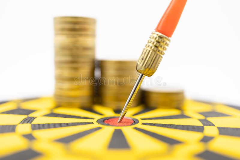 Money, Game, Business, Planning and Target Concept.  Close up of dart stab on center of black and yellow board with stack of gold. Coins on white background stock photography