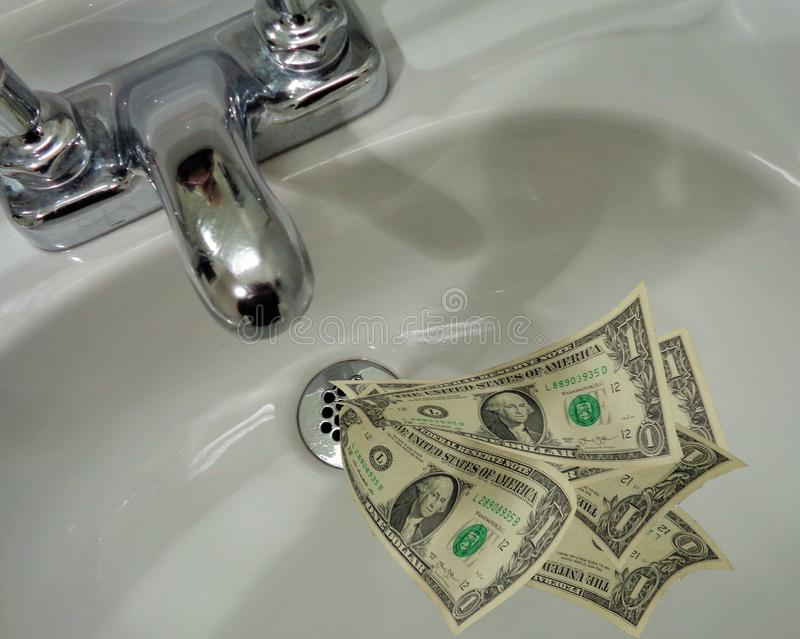 Money Going Down the Drain. This image illustrates the English language idiom & x22;Money Going Down the Drain& x22;. It shows United States One Dollar bills royalty free stock image