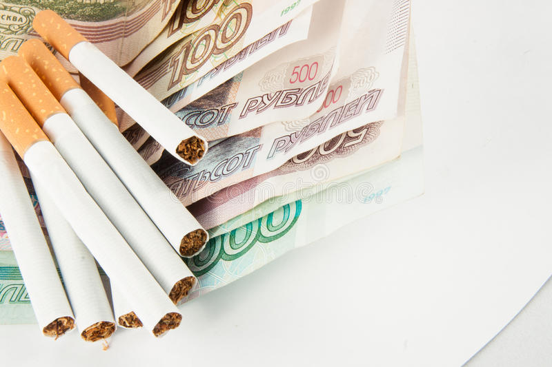 Money and group of cigarettes. On white royalty free stock photo