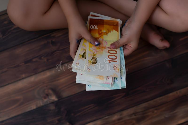 Money in the hand child, Concept Investment in real estate finance. israeli shekel. Holding a shekel in his hand and thinking how to spend money stock images