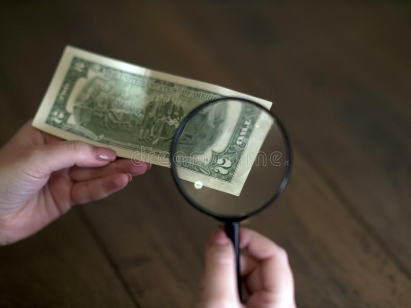 Hand holds happy two dollars, viewed through a magnifying glass stock photos