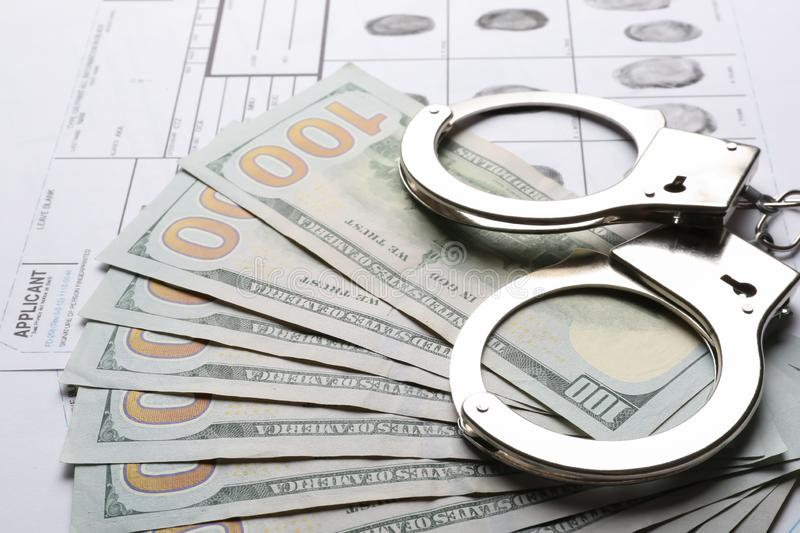 Money, handcuffs and fingerprint record sheets, closeup. Criminal investigation royalty free stock photography