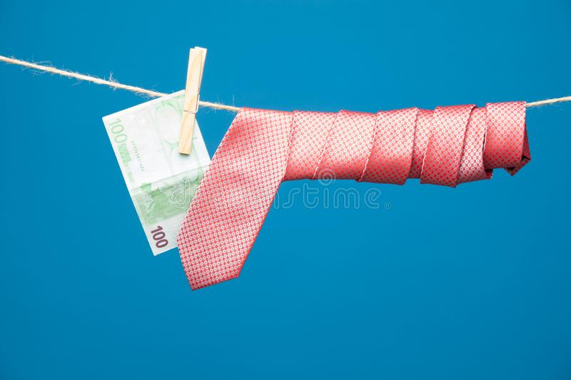 Tongs, money and tie with knot, on a rope. Money hanging on a rope and held by a wooden clamp, a clothespin and hanging clothes. Ticket of legal tender, money in royalty free stock photos