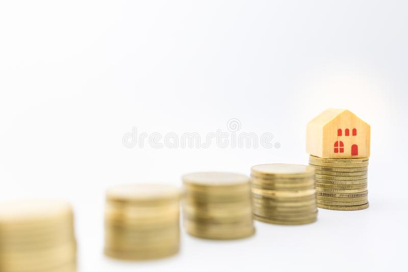 Money, Home Loan, Business and Finance concept. Close up of wooden house toy on top of stack of golc coins on white background and. Copy space stock image