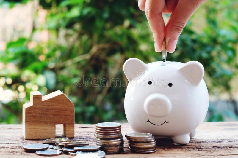 Money for housing. Putting each coin into a piggy bank. Wooden house model and money with greenery background stock photography