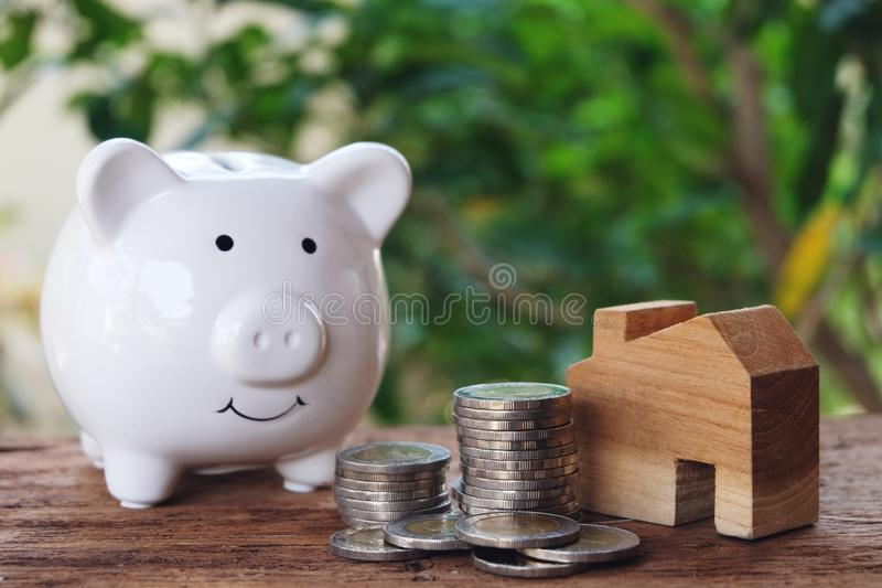 Money for housing. Wooden house model, piggy bank and pile of coins with greenery background. Copy space stock photos