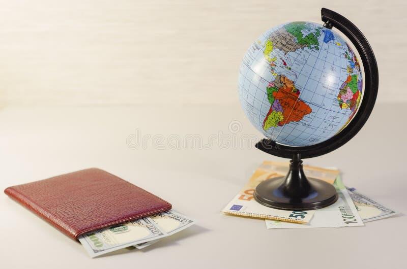 Money inside passport and globe 2.  royalty free stock photo