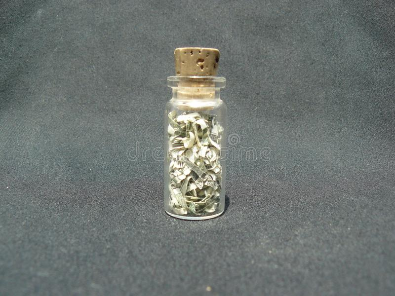 Money in a Jar with a cork. One dollar in pieces inside a small jar covered with a cork royalty free stock image