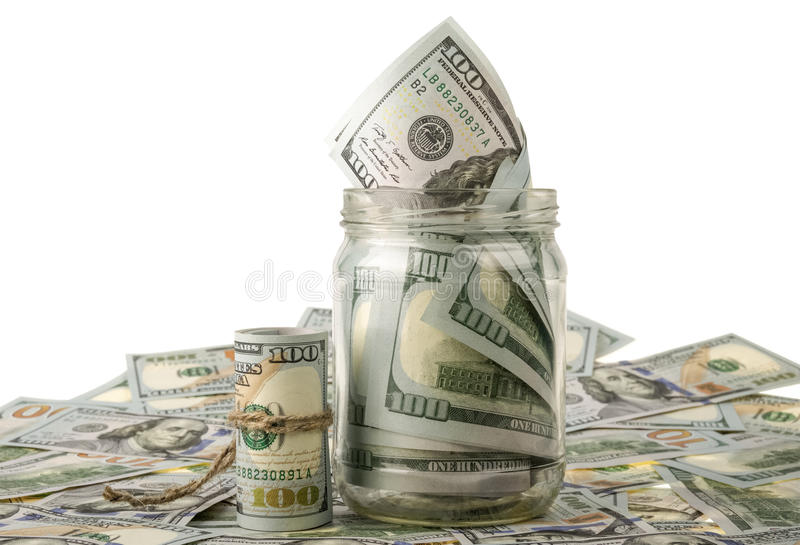 Money in the jar placing on US dollar banknotes. Money in the jar placing on USA dollar banknotes royalty free stock photos