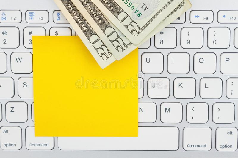 Money on a keyboard with sticky note. Money on a computer keyboard with sticky note for your making money message stock photo